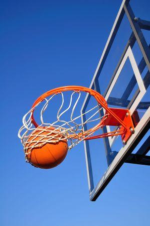 shot: Basketball Shot Falling Through the Net, Blue Sky, vertical, copy space