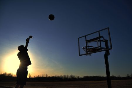 Silhouette of a Teen Boy Shooting a Basketball at Sunset, copy space