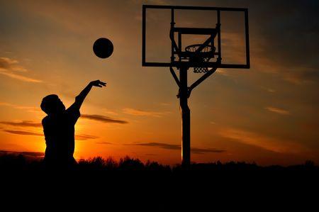 basket: Silhouette di una ragazza Boy uno Basket Shooting at Sunset, copia spazio