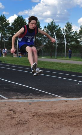 Teen Boy doing the Triple Jump at a High School Track and Field Meet, copy space, vertical Stock Photo
