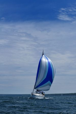Sailboat with blue spinnaker Sail on a beautiful summer day, vertical
