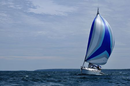 spinnaker: Sailboat with blue spinnaker Sail on a beautiful summer day, horizontal