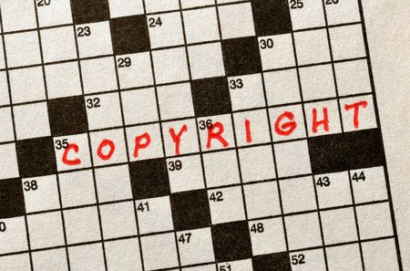 The Word COPYRIGHT on Crossword Puzzle in Red Ink Stock Photo
