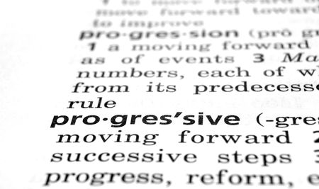 progressively: The word Progressive in a dictionary, close-up