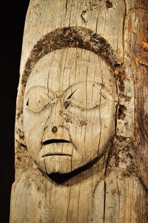 Old, Weathered Tlingit Totem Pole with Human Face located in Ketchika, Alaska, Vertical photo