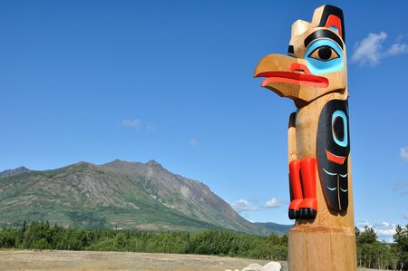 tlingit: Eagle Totem Pole Against a Blue Sky located in Carcross, Yukon, Canada, Copy Space Stock Photo