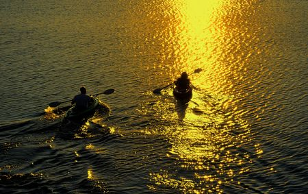couple lit: Silhouette of Man and Woman Kayaking on a Lake at Sunset Stock Photo