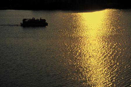석양에 호수에서 자동차를 타는 폰툰 보트의 실루엣 스톡 콘텐츠