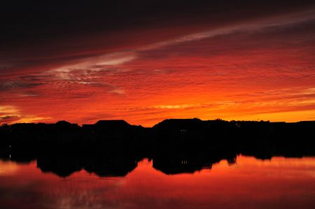 Silhouettes and Reflections of Suburban Lake Homes at Sunset Stock Photo - 5432713