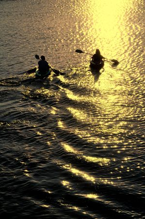 Silhouette of Man and Woman Kayaking on a Lake at Sunset Stock Photo