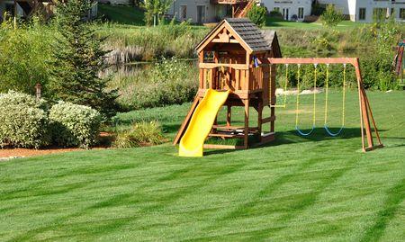 Back Yard Wooden Swing Set on Green Lawn photo