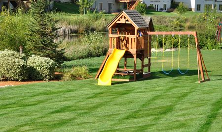 jungle gyms: Back Yard Wooden Swing Set on Green Lawn Stock Photo