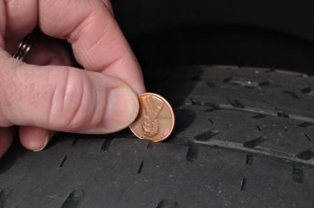 pisada: Inspeccionar el desgaste de un Uisng de la banda de rodadura de calvicie neum�tico un centavo