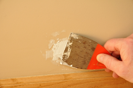 putty knives: Putty Knite with Spackling Paste to Repair Wall Damage Stock Photo