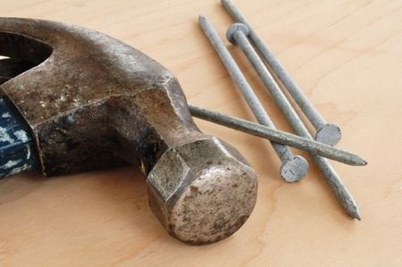 metal fastener: Galvanized Nails and a Claw Hammer on a Wooden Board