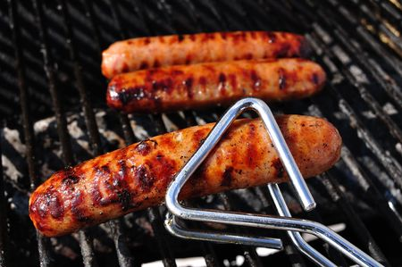 Bratwurst on the grill with Tongs, copy space