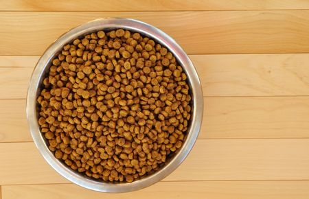 Dry Dog Food in a Stainless Steel Bowl on Hardword Floor photo