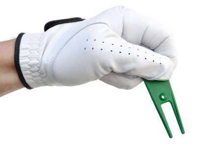 緑色のボール マーク修復ツール (またはフォーク) を保持しているゴルファー