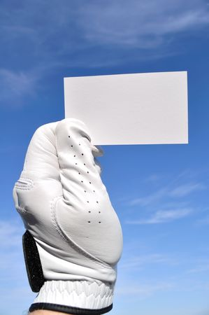 Golfer Wearing Golf Glove Holding a Blank Business Card Against a Blue Sky Stock Photo - 6695544