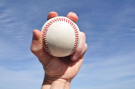 grasp: Player Gripping a New Baseball Against a Blue Sky