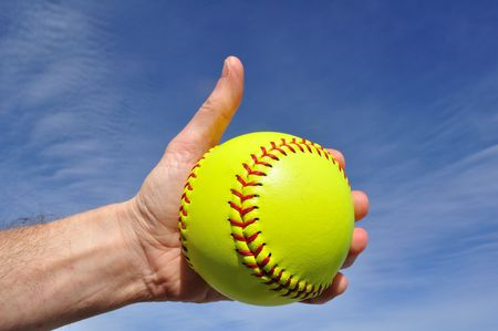 alright: Softball Player Giving Thumbs Up Sign Against a Blue Sky