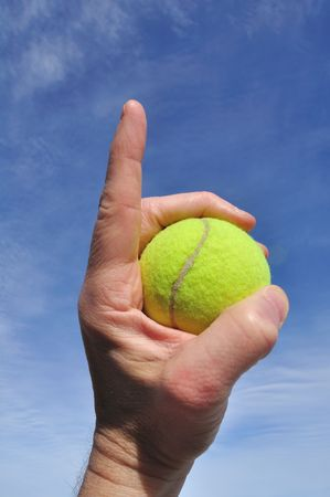 Player Gripping a Yellow Tennis Ball Doing Number One Sign Banco de Imagens