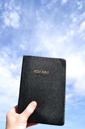 Hand Lifting Holy Bible to the Sky, Copy Space photo