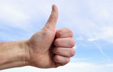 alright: Man Giving Thumbs Up Sign Against a Blue Sky Stock Photo