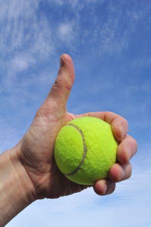 Tennis Player Giving Thumbs Up Sign gegen einen blauen Himmel