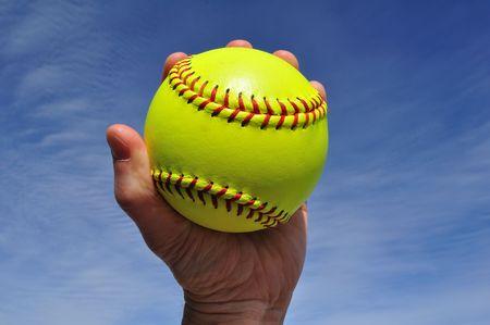 Player Gripping a Yellow Softball Against a Blue Sky Banco de Imagens