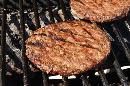 Hamburgers cooking on the grill, copy space photo