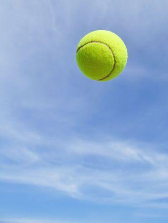 青空に対して空気の黄色いテニスボール