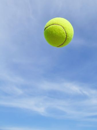 Yellow Tennis Ball in the Air Against a Blue Sky Stock Photo
