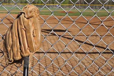 Baseball Bat and Glove Leaning Against the Backstop Stock Photo - 6911776
