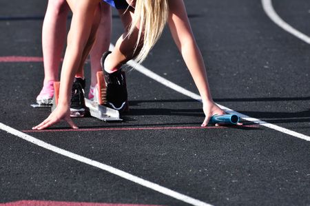 relay baton: Teen Girl in the Starting Blocks at a Track Meet