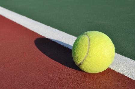 ベースライン テニス裁判所の近くの黄色いテニスボール