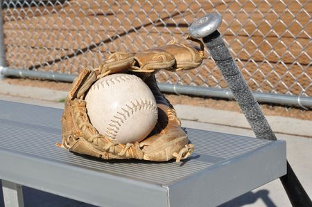 backstop: White Softball, Bat, and Glove on an Aluminum Bench
