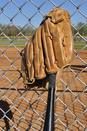Baseball Bat and Glove Leaning Against the Backstop photo