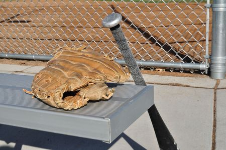 Baseball Bat and Glove on an Aluminum Bench photo