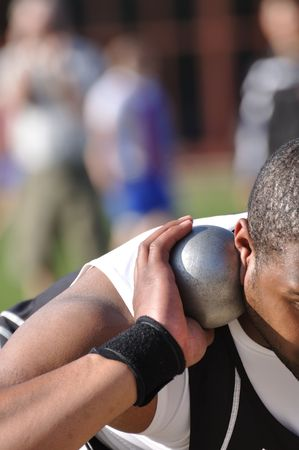 Man Preparing to Toss Shot Put at a Track and Field Meet photo
