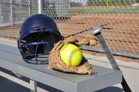 softball: Amarillo Softbol, casco, bat y guante en un banco de aluminio