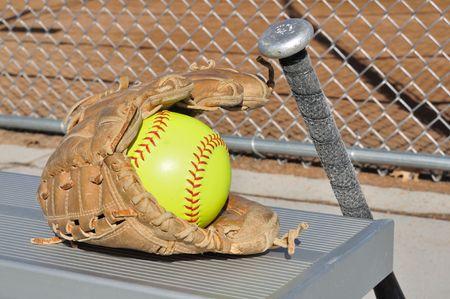 黄色のソフトボール、バットとアルミニウム ベンチの手袋 写真素材