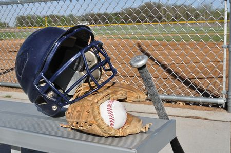 Baseball, Helmet, Bat, and Glove on an Aluminum Bench photo
