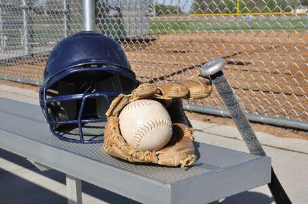 backstop: White Softball, Helmet, Bat, and Glove on an Aluminum Bench