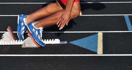 relevos: Boy adolescente salir de los bloques de inicio en el inicio de una carrera