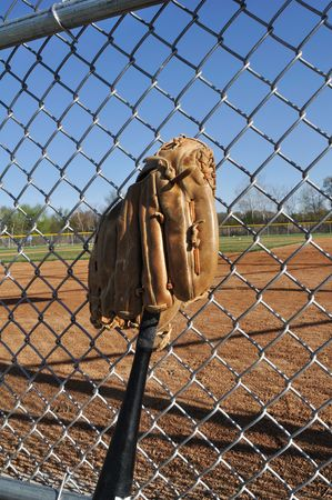backstop: Baseball Bat and Glove Leaning Against the Backstop