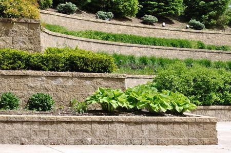 En niveles de retención Wall con host y arbustos