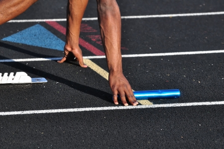 Teen Boy in the Starting Blocks for a Relay Race photo