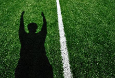 Schaduw van Amerikaanse voet bal scheidsrechter signalering een Touchdown Stockfoto