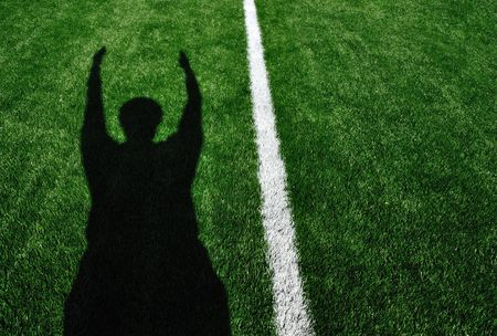 Shadow of American Football Referee Signaling a Touchdown Banco de Imagens
